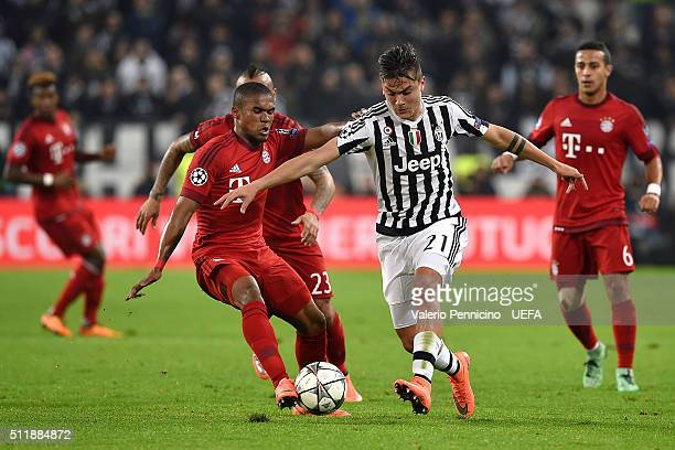 Paulo Dybala of Juventus competes with Douglas Costa of FC Bayern Muenchen during the UEFA Champions League Round of 16 first leg match between...