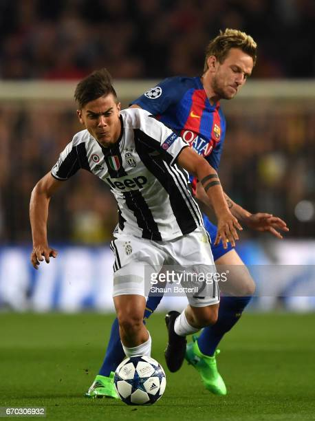Paulo Dybala of Juventus escapes a challenge from Ivan Rakitic of Barcelona during the UEFA Champions League Quarter Final second leg match between...