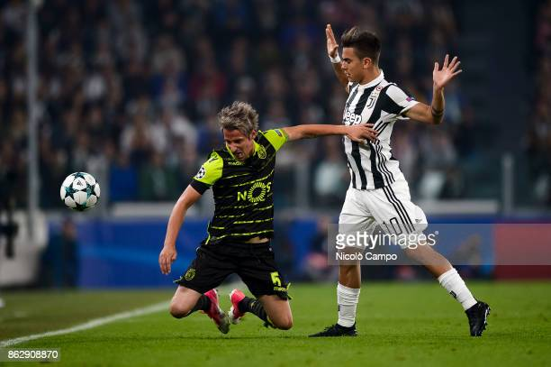 Paulo Dybala of Juventus FC compete with Fabio Coentrao of Sporting CP during the UEFA Champions League football match between Juventus FC and...
