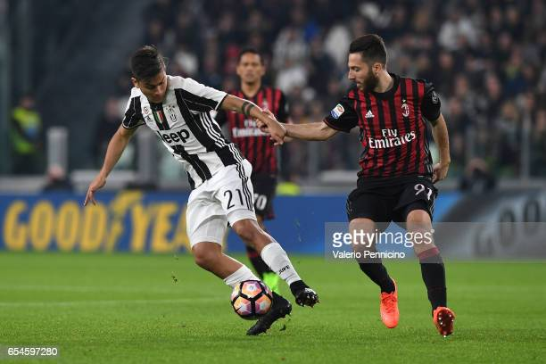 Paulo Dybala of Juventus FC is challenged by Andrea Bertolacci of AC Milan during the Serie A match between Juventus FC and AC Milan at Juventus...