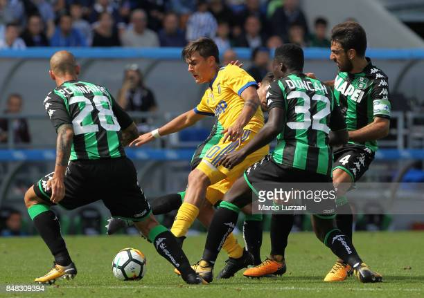 Paulo Dybala of Juventus is challenged by Alfred Duncan Paolo Cannavaro and Francesco Magnanelli of US Sassuolo Calcio during the Serie A match...
