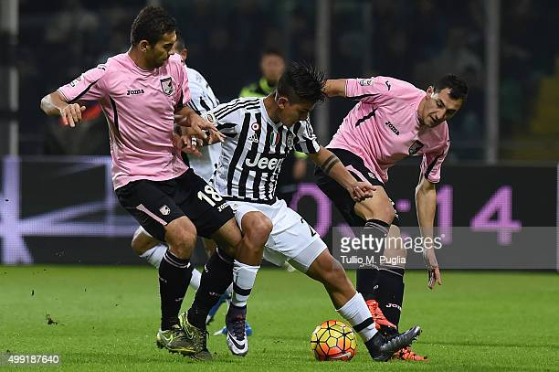 Paulo Dybala of Juventus is challenged by Ivaylo Chochev and Mato Jajalo of Palermo during the Serie A match between US Citta di Palermo and Juventus...