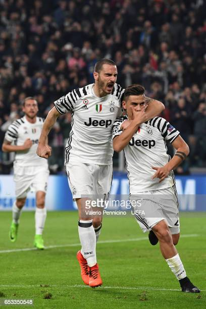 Paulo Dybala of Juventus scores the opening goal with team mate Leonardo Bonucci during the UEFA Champions League Round of 16 second leg match...