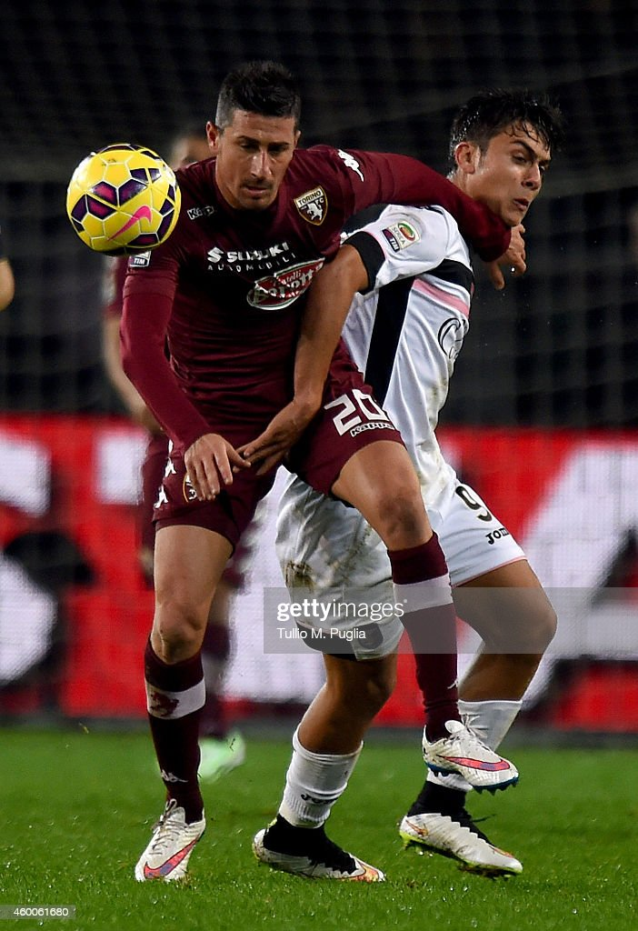 Paulo Dybala (L) of Palermo and Giuseppe Vives of Torino compete for the ball during the Serie A match between Torino FC and US Citta di Palermo at Stadio Olimpico di Torino on December 6, 2014 in Turin, Italy.