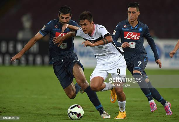 Paulo Dybala of Palermo is challenged by Raul Albiol and Jose Maria Callejon during the Serie A match between SSC Napoli and US Citta di Palermo at...