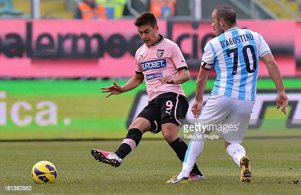 Paulo Dybala of Palermo kicks the ball as Gaetano D'agostino of Pescara tackles during the Serie A match between US Citta di Palermo and Pescara at...