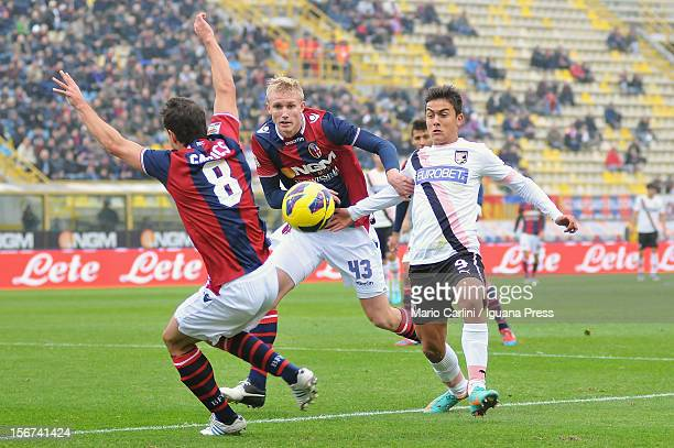 Paulo Dybala of US Citta di Palermo competes for the ball with Frederick Sorensen of Bologna FC and Gyorgy Garics of Bologna FC during the Serie A...