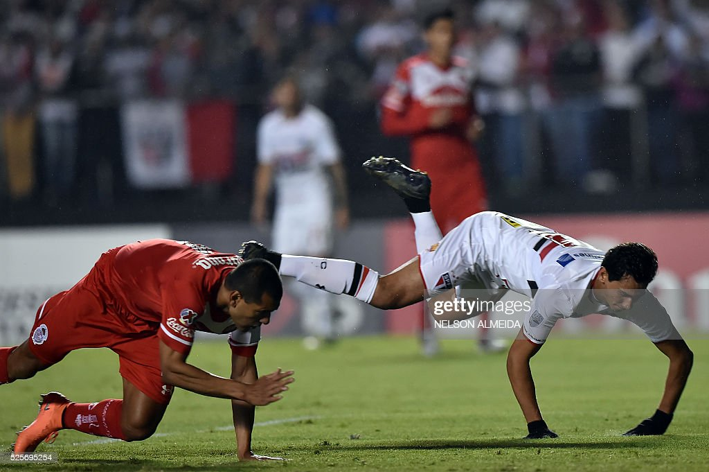 Paulo Henrique Ganso (R) of Brazils Sao Paulo, vies for the ball with Paulo Cesar Da Silva (L)of Mexico's Toluca during their 2016 Copa Libertadores football match held at Morumbi stadium, in Sao Paulo, Brazil, on April 28, 2016. / AFP / NELSON