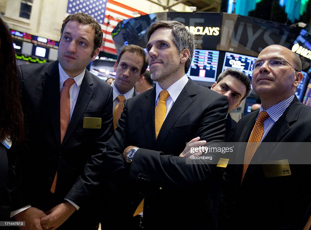 Paulo Sergio Kakinoff, chief executive officer of Gol Linhas Aereas Inteligentes SA, center, stands with other executives while looking at stock activity on the floor of the New York Stock Exchange (NYSE) in New York, U.S., on Monday, June 24, 2013. U.S. stocks fell after Chinese equities entered a bear market on concern a cash crunch will hurt growth. Treasuries pared losses on speculation investors overreacted to a possible reduction of central bank stimulus. Photographer: Jin Lee/Bloomberg via Getty Images
