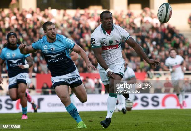 Pau's Fijian winger Watisonu Votu passes the ball as Montpellier's South African centre Francois Steyn runs during the French Top 14 rugby union...