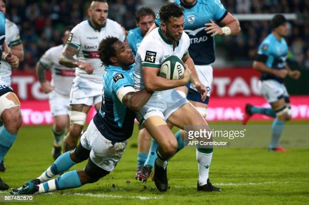 Pau's NewZealander fullback Tom Taylor is tackled by Montpellier's French winger Benjamin Fall during the French Top 14 rugby union match between Pau...