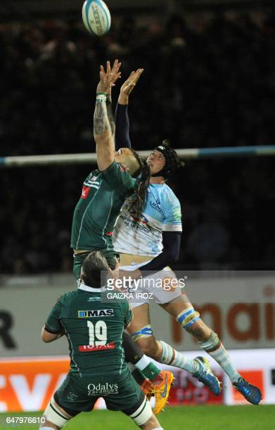 Pau's replacement Pierrick Gunther and Bayonne's French flanker Baptiste Chouzenoux jump to grab the ball during the French Top 14 rugby union match...
