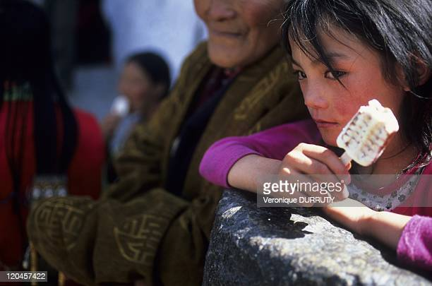 A pause in the pilgrimage little girl eating an icecream near Jokhang temple Tibet in Lhasa China