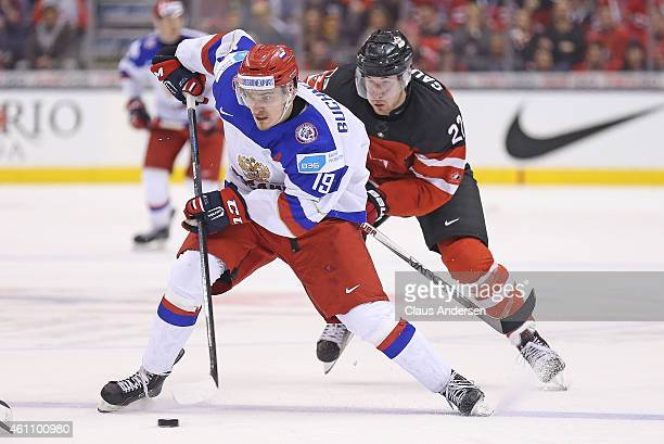Pavel Buchnevich of Team Russia tries to break clear of Fredrik Gauthier of Team Canada during the gold medal game in the 2015 IIHF World Junior...