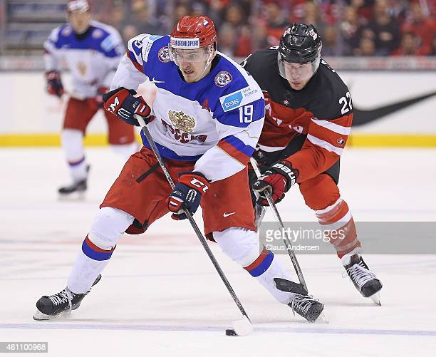 Pavel Buchnevich of Team Russia tries to skate clear of Fredrik Gauthier of Team Canada during the gold medal game in the 2015 IIHF World Junior...