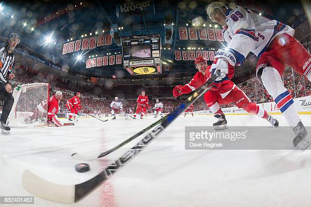 Pavel Buchnevich of the New York Rangers battles for the puck along the boards with Nick Jensen of the Detroit Red Wings during an NHL game at Joe...