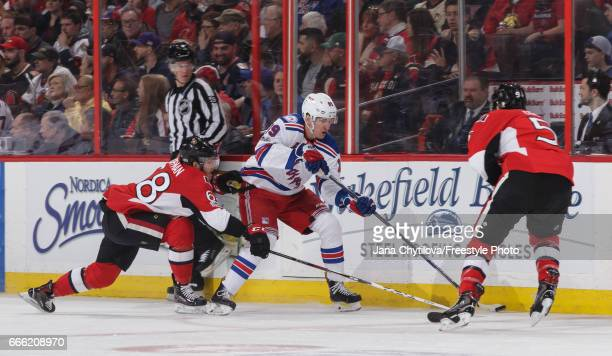 Pavel Buchnevich of the New York Rangers skates with the puck against Mike Hoffman and Cody Ceci of the Ottawa Senators in the first period at...
