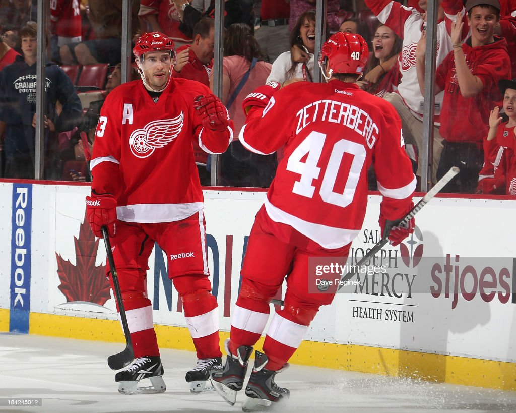 <a gi-track='captionPersonalityLinkClicked' href=/galleries/search?phrase=Pavel+Datsyuk&family=editorial&specificpeople=202893 ng-click='$event.stopPropagation()'>Pavel Datsyuk</a> #13 and <a gi-track='captionPersonalityLinkClicked' href=/galleries/search?phrase=Henrik+Zetterberg&family=editorial&specificpeople=201520 ng-click='$event.stopPropagation()'>Henrik Zetterberg</a> #40 of the Detroit Red Wings bump gloves after an empty net goal to clinch the victory during a NHL game at Joe Louis Arena on October 12, 2013 in Detroit, Michigan. Detroit defeated Philadelphia 5-2.