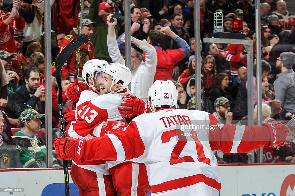 <a gi-track='captionPersonalityLinkClicked' href=/galleries/search?phrase=Pavel+Datsyuk&family=editorial&specificpeople=202893 ng-click='$event.stopPropagation()'>Pavel Datsyuk</a> #13 and <a gi-track='captionPersonalityLinkClicked' href=/galleries/search?phrase=Tomas+Tatar&family=editorial&specificpeople=5652303 ng-click='$event.stopPropagation()'>Tomas Tatar</a> #21 celebrate with <a gi-track='captionPersonalityLinkClicked' href=/galleries/search?phrase=Darren+Helm&family=editorial&specificpeople=3949334 ng-click='$event.stopPropagation()'>Darren Helm</a> #43 of the Detroit Red Wings after Helm scored against the Chicago Blackhawks in the third period during the NHL game at the United Center on February 18, 2015 in Chicago, Illinois.
