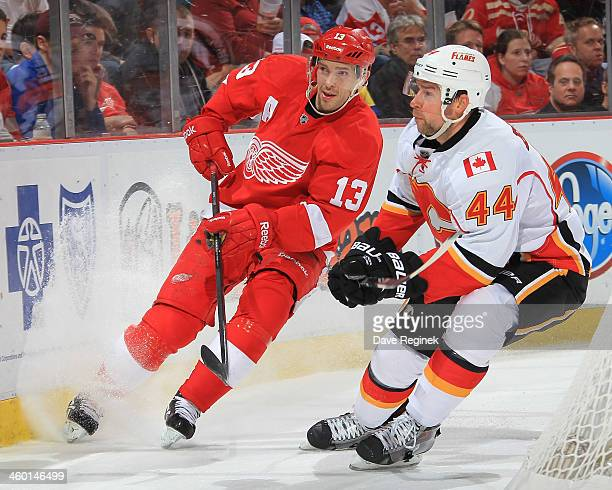 Pavel Datsyuk of the Detroit Red Wings and Chris Butler of the Calgary Flames skates after a loose puck during an NHL game at Joe Louis Arena on...
