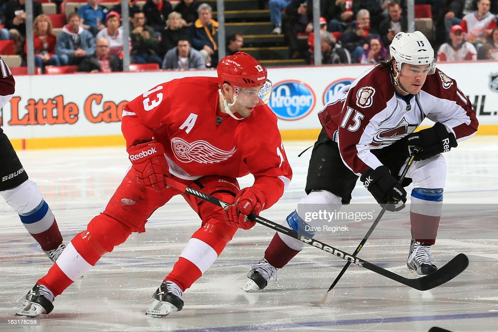 Pavel Datsyuk #13 of the Detroit Red Wings and PA Parenteau #15 of the Colorado Avalanche race for the puck during a NHL game at Joe Louis Arena on March 5, 2013 in Detroit, Michigan.