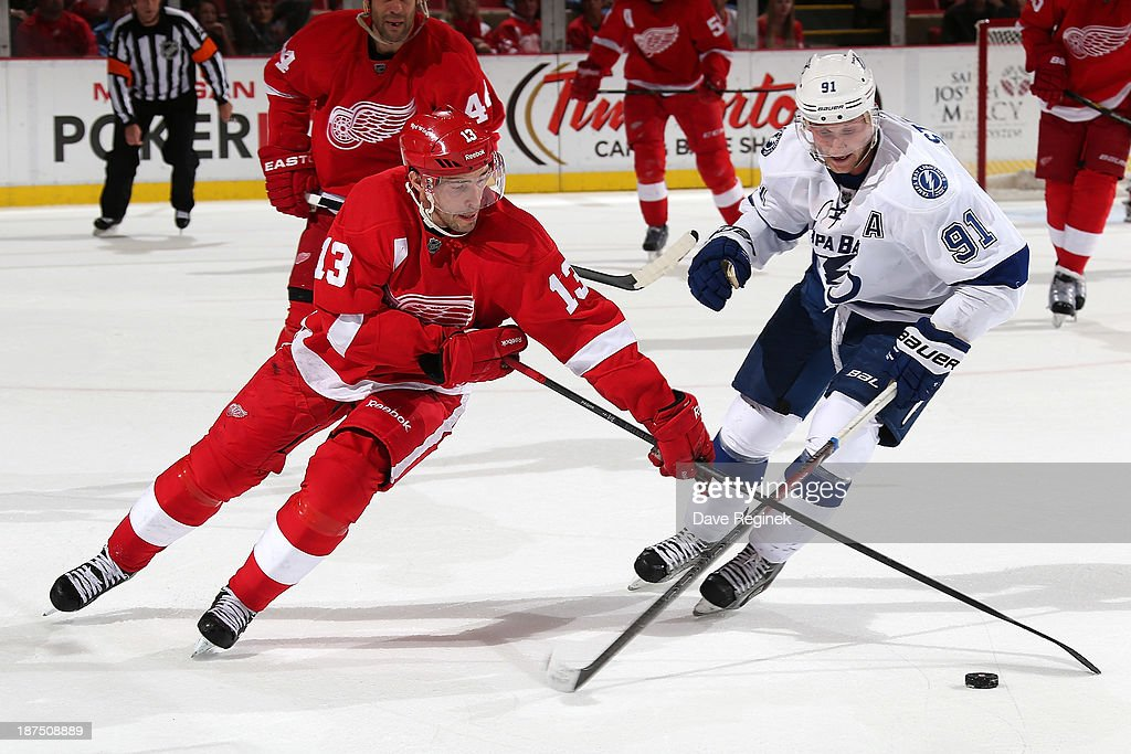 Pavel Datsyuk #13 of the Detroit Red Wings and Steven Stamkos #91 of the Tampa Bay Lightning battle for the puck during an NHL game at Joe Louis Arena on November 9, 2013 in Detroit, Michigan. Tampa Bay defeated Detroit 3-2 in OT