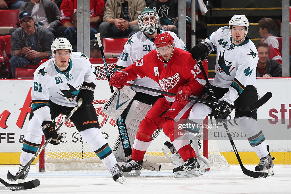 <a gi-track='captionPersonalityLinkClicked' href=/galleries/search?phrase=Pavel+Datsyuk&family=editorial&specificpeople=202893 ng-click='$event.stopPropagation()'>Pavel Datsyuk</a> #13 of the Detroit Red Wings battles for position in front of <a gi-track='captionPersonalityLinkClicked' href=/galleries/search?phrase=Antti+Niemi&family=editorial&specificpeople=213913 ng-click='$event.stopPropagation()'>Antti Niemi</a> #31 of the San Jose Sharks while teammates Justin Braun #61 and <a gi-track='captionPersonalityLinkClicked' href=/galleries/search?phrase=Marc-Edouard+Vlasic&family=editorial&specificpeople=880807 ng-click='$event.stopPropagation()'>Marc-Edouard Vlasic</a> #44 of the Sharks help to defend during an NHL game at Joe Louis Arena on October 21, 2013 in Detroit, Michigan.