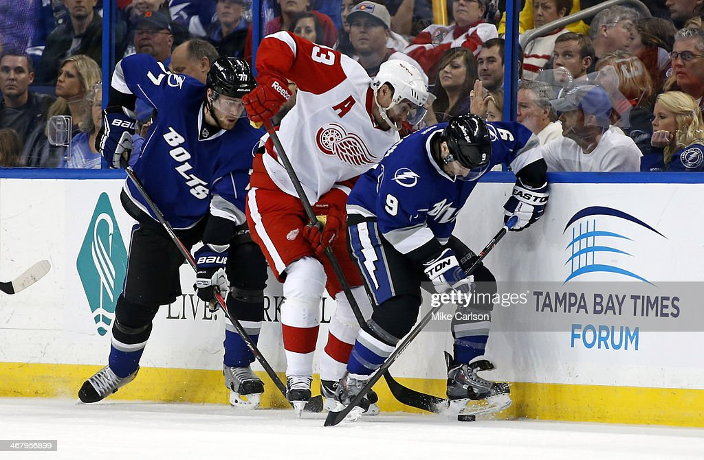<a gi-track='captionPersonalityLinkClicked' href=/galleries/search?phrase=Pavel+Datsyuk&family=editorial&specificpeople=202893 ng-click='$event.stopPropagation()'>Pavel Datsyuk</a> #13 of the Detroit Red Wings fights for the puck between <a gi-track='captionPersonalityLinkClicked' href=/galleries/search?phrase=Victor+Hedman&family=editorial&specificpeople=4784238 ng-click='$event.stopPropagation()'>Victor Hedman</a> #77 and <a gi-track='captionPersonalityLinkClicked' href=/galleries/search?phrase=Tyler+Johnson+-+Ice+Hockey+Player&family=editorial&specificpeople=14574766 ng-click='$event.stopPropagation()'>Tyler Johnson</a> #9 of the Tampa Bay Lightning at the Tampa Bay Times Forum on February 8, 2014 in Tampa, Florida.