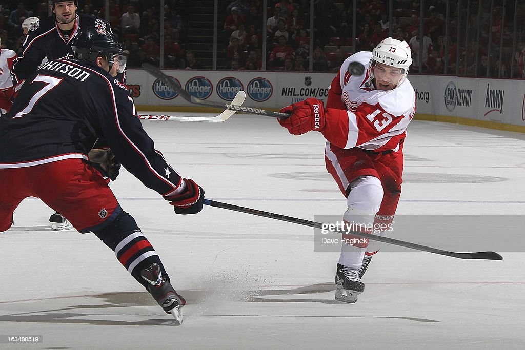 <a gi-track='captionPersonalityLinkClicked' href=/galleries/search?phrase=Pavel+Datsyuk&family=editorial&specificpeople=202893 ng-click='$event.stopPropagation()'>Pavel Datsyuk</a> #13 of the Detroit Red Wings has a shot deflect off of the stick of Jack Johnson #7 of the Columbus Blue Jackets during an NHL game at Joe Louis Arena on March 10, 2013 in Detroit, Michigan. Columbus won 3-2 in a shoot-out