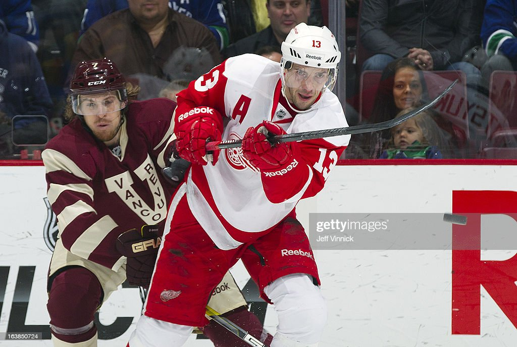 <a gi-track='captionPersonalityLinkClicked' href=/galleries/search?phrase=Pavel+Datsyuk&family=editorial&specificpeople=202893 ng-click='$event.stopPropagation()'>Pavel Datsyuk</a> #13 of the Detroit Red Wings plays the puck in front of <a gi-track='captionPersonalityLinkClicked' href=/galleries/search?phrase=David+Booth+-+Ice+Hockey+Player&family=editorial&specificpeople=1109572 ng-click='$event.stopPropagation()'>David Booth</a> #7 of the Vancouver Canucks during their NHL game at Rogers Arena March 16, 2013 in Vancouver, British Columbia, Canada. Detroit won 5-2.