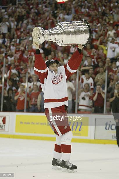 Pavel Datsyuk of the Detroit Red Wings raises the Stanley Cup after eliminating the Carolina Hurricanes during game five of the NHL Stanley Cup...