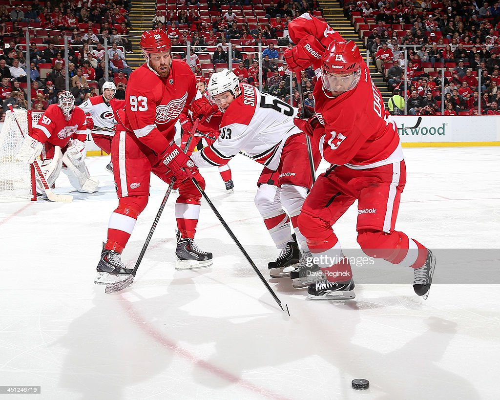 <a gi-track='captionPersonalityLinkClicked' href=/galleries/search?phrase=Pavel+Datsyuk&family=editorial&specificpeople=202893 ng-click='$event.stopPropagation()'>Pavel Datsyuk</a> #13 of the Detroit Red Wings skates around teammate <a gi-track='captionPersonalityLinkClicked' href=/galleries/search?phrase=Johan+Franzen&family=editorial&specificpeople=624356 ng-click='$event.stopPropagation()'>Johan Franzen</a> #93 and <a gi-track='captionPersonalityLinkClicked' href=/galleries/search?phrase=Jeff+Skinner&family=editorial&specificpeople=3147596 ng-click='$event.stopPropagation()'>Jeff Skinner</a> #53 of the Carolina Hurricanes to find the puck during an NHL game at Joe Louis Arena on November 21, 2013 in Detroit, Michigan.