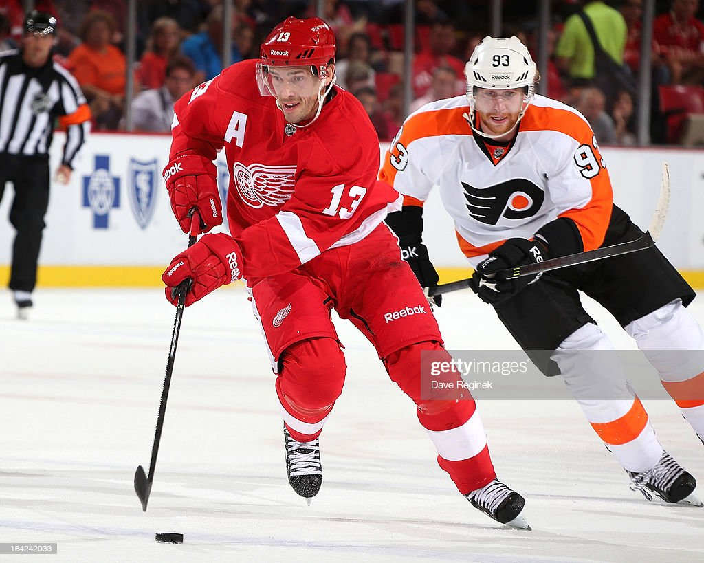 <a gi-track='captionPersonalityLinkClicked' href=/galleries/search?phrase=Pavel+Datsyuk&family=editorial&specificpeople=202893 ng-click='$event.stopPropagation()'>Pavel Datsyuk</a> #13 of the Detroit Red Wings skates with the puck as <a gi-track='captionPersonalityLinkClicked' href=/galleries/search?phrase=Jakub+Voracek&family=editorial&specificpeople=4111797 ng-click='$event.stopPropagation()'>Jakub Voracek</a> #93 of the Philadelphia Flyers gives chase during a NHL game at Joe Louis Arena on October 12, 2013 in Detroit, Michigan.