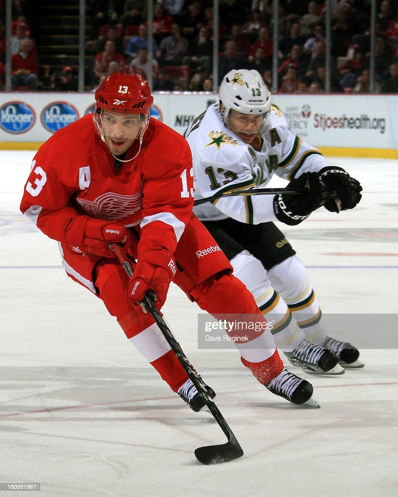 <a gi-track='captionPersonalityLinkClicked' href=/galleries/search?phrase=Pavel+Datsyuk&family=editorial&specificpeople=202893 ng-click='$event.stopPropagation()'>Pavel Datsyuk</a> #13 of the Detroit Red Wings skates with the puck as <a gi-track='captionPersonalityLinkClicked' href=/galleries/search?phrase=Ray+Whitney&family=editorial&specificpeople=202090 ng-click='$event.stopPropagation()'>Ray Whitney</a> #13 of the Dallas Stars hooks him during an NHL game at Joe Louis Arena on January 29, 2013 in Detroit, Michigan. Detroit defeated Dallas 4-1