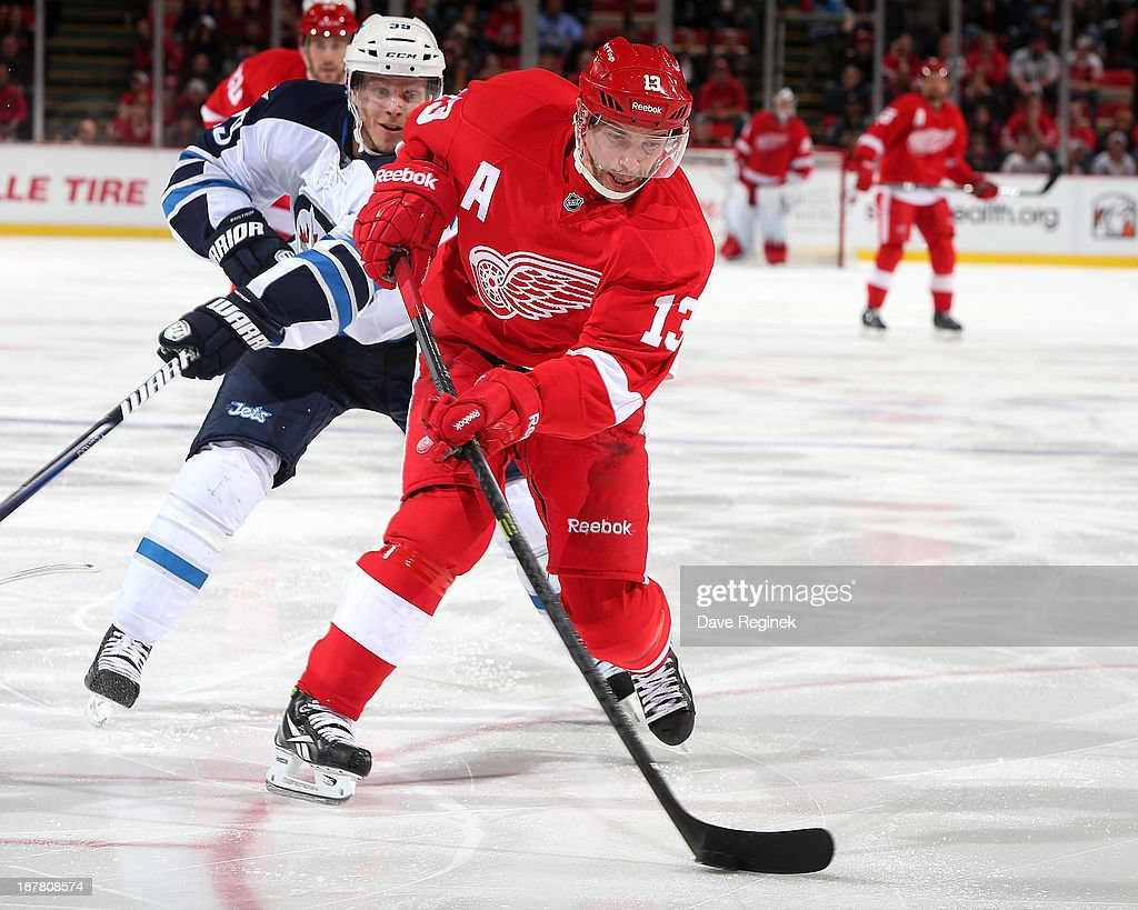 Pavel Datsyuk #13 of the Detroit Red Wings skates with the puck as Tobias Enstrom #39 of the Winnipeg Jets tries to defend him during an NHL game at Joe Louis Arena on November 12, 2013 in Detroit, Michigan.