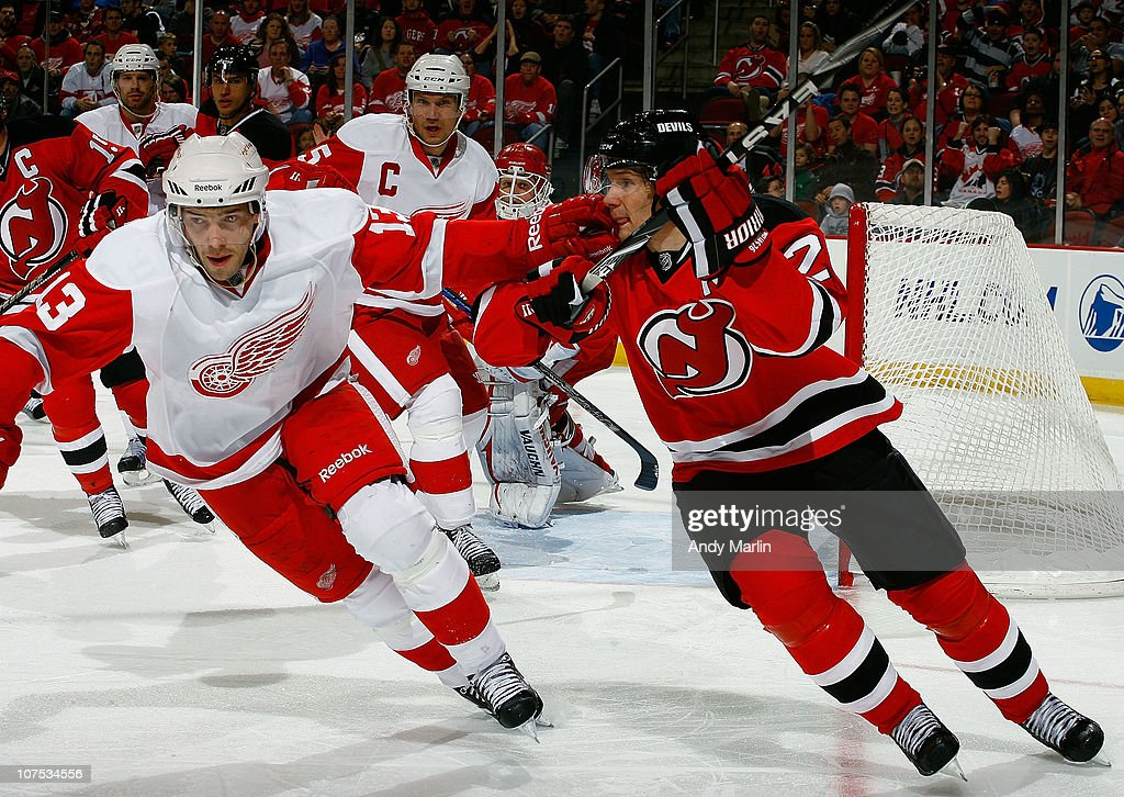 Pavel Datysuk #13 of the Detroit Red Wings and Patrik Elias #26 of the New Jersey Devils skate hard during the game at the Prudential Center on December 11, 2010 in Newark, New Jersey.