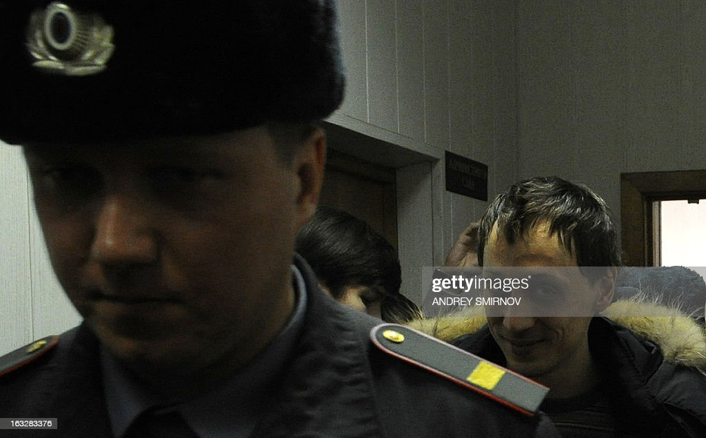 Pavel Dmitrichenko, a leading dancer at Russia's Bolshoi Theatre, smiles as he is escorted into a court in Moscow on March 7, 2013. Dmitrichenko appeared today in court after confessing to planning the acid attack on the ballet troupe's artistic director Sergei Filin, reportedly in revenge for his treatment of his dancer girlfriend. AFP PHOTO / ANDREY SMIRNOV
