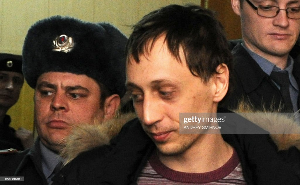 Pavel Dmitrichenko, a leading dancer at Russia's Bolshoi Theatre, smiles as he is escorted into a court in Moscow on March 7, 2013. Dmitrichenko admitted today in court that he ordered an assault on the famed Russian ballet troupe's artistic director but denied ever planning the use of acid to ruin his sight. AFP PHOTO / ANDREY SMIRNOV