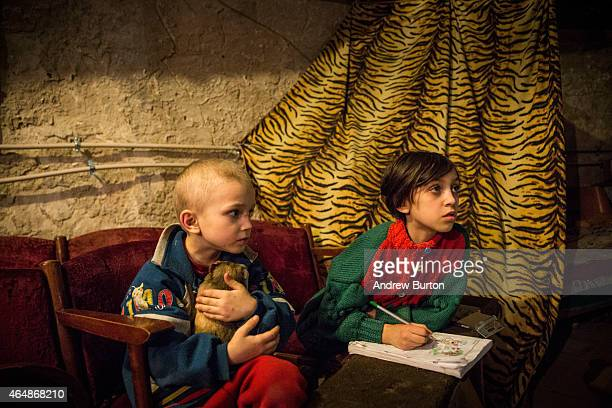 Pavel Makeev age five and Raya Makeeva age seven play while waiting for lunch to be cooked in the basement of the Petrovskiy neighborhood cultural...