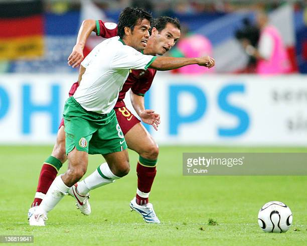 Pavel Prado struggles with Petit for the ball during the Group D match between Portugal and Mexico at FIFA World Cup stadium Gelsenkirchen Germany on...