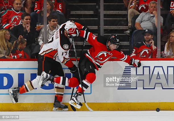 Pavel Zacha of the New Jersey Devils is tripped up by Ryan Kesler of the Anaheim Ducks during the first period at the Prudential Center on October 18...