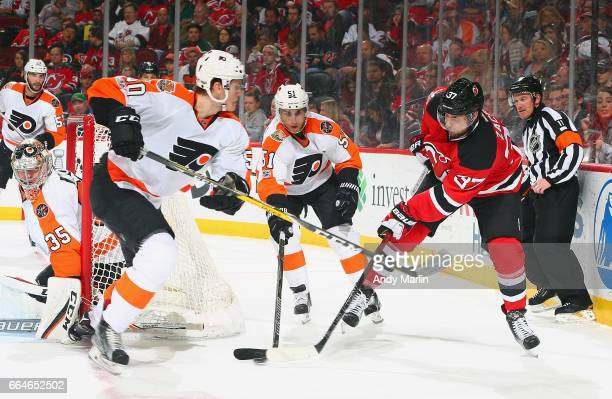 Pavel Zacha of the New Jersey Devils Samuel Morin playing in his first NHL game and Valtteri Filppula of the Philadelphia Flyers battle for a loose...