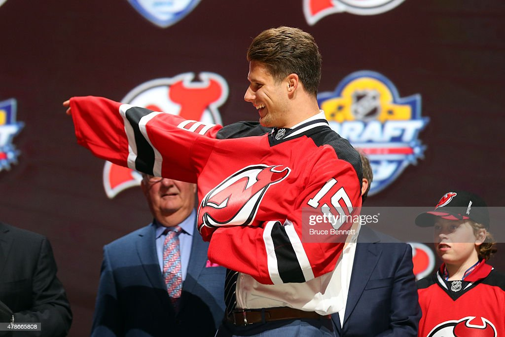 Pavel Zacha puts on his jersey after being selected sixth overall by the New Jersey Devils in the first round of the 2015 NHL Draft at BB&T Center on June 26, 2015 in Sunrise, Florida.
