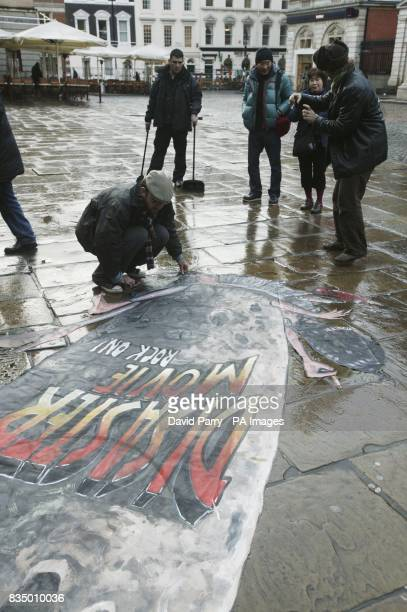 Pavement artist Joe Hill adds the final touches to his 3D pavement art in Covent Garden London to mark the launch of Disaster Movie the latest...