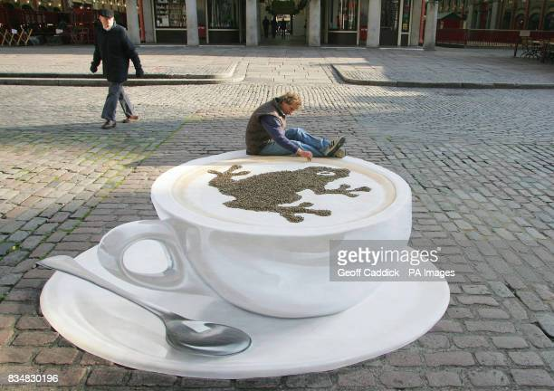 Pavement artist Manfred Stader creates a giant 3D coffee cup in London's Covent Garden Piazza for Costa Coffee