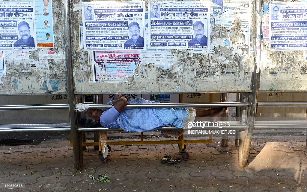 A pavement dweller takes a nap at a bus shelter in Mumbai on January 30, 2013. Mumbai, though being India's financial capital houses more than 100 000 homeless people on its streets, most of them being migrants from various parts of the country who come to Mumbai to make a living. AFP PHOTO/Indranil MUKHERJEE