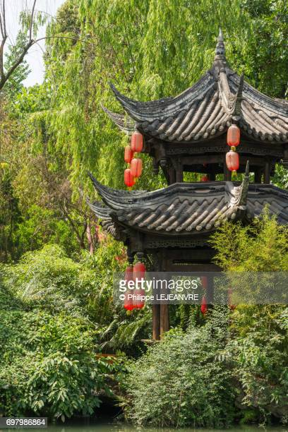 Pavilion with red chinese lanterns among trees by a pond