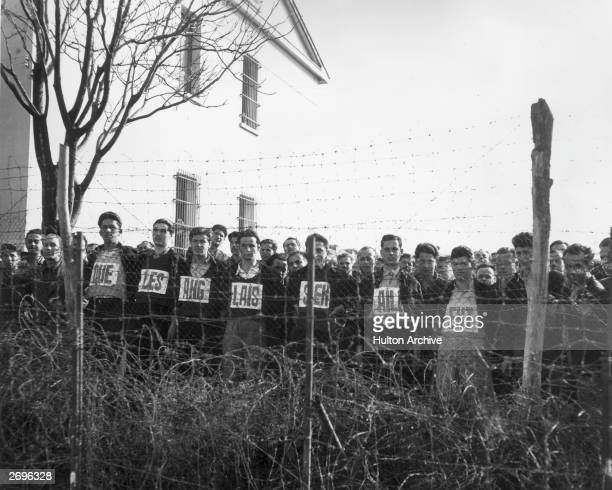 Pavlos Hellas political prisoners lined up behind barbed wire with 'The British Must Go' spelled out in French on their shirts Greek Civil War...