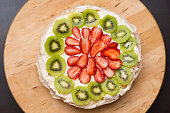 Pavlova Cake Traditional Iconic Australian Dessert. Homemade Meringue Pie Decorated with Fresh Fruit Strawberry and Kiwi