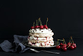 Pavlova cake with fresh cherry, cheese cream and chocolate chips in vintage silver plate over dark grunge backdrop